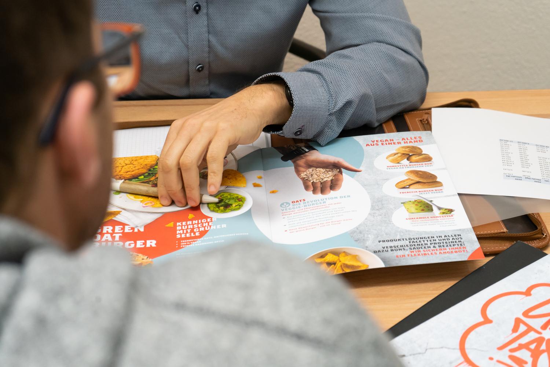 2 Personen in einem Lebensmittelgroßhandel besprechen den neuen Produktkatalog.