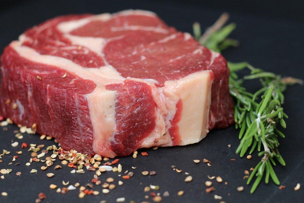 Fleisch Großhandel Produkt mit Kräutern. Platziert ist das Fleisch auf einem schwarzen Hintergrund.
