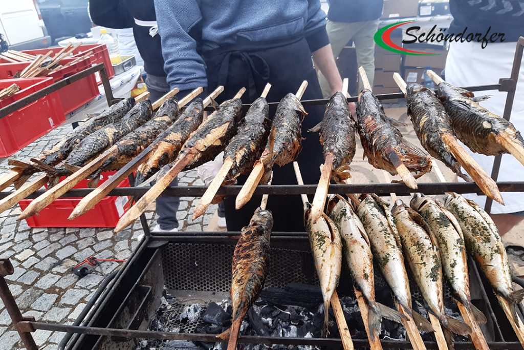 Fisch Großhandel Produkte: Steckerlfisch auf Holz gespielßt über dem Grillfeuer.