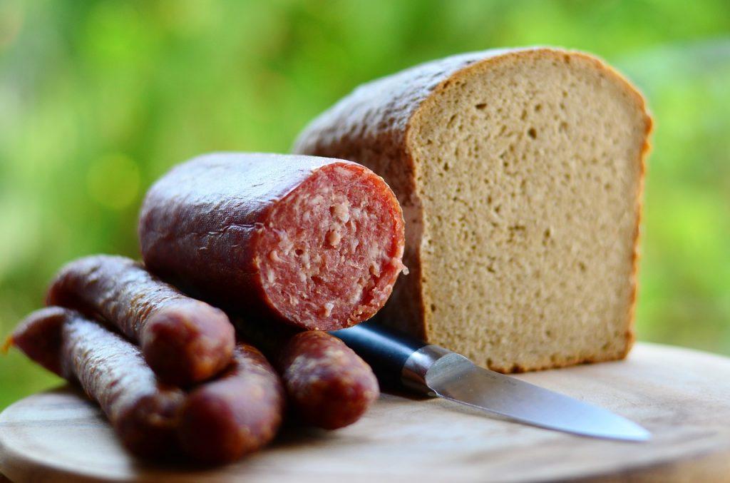 Fleisch & Wurst Großhandel. Jausenwurst auf eiem Holzbrett mit einem angeschnittenen Laib Brot
